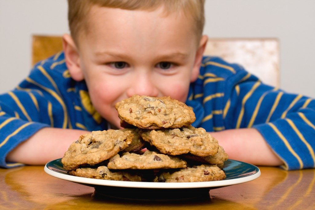 Kid looking at cookies on a plate