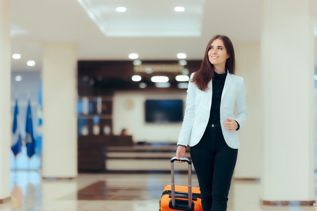 woman holding a suitcase walking inside the airport