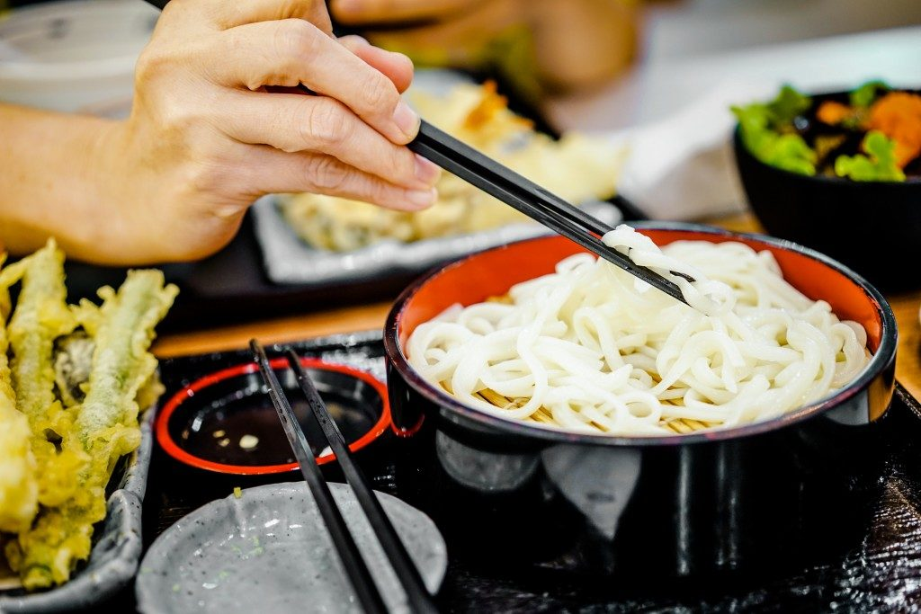 women hand using chopstick eat noodle